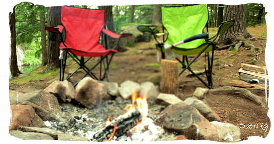 Camping chairs, an axe and firewood at camp fire